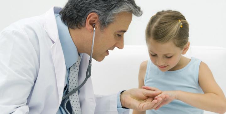 En læge der behandler et barn.