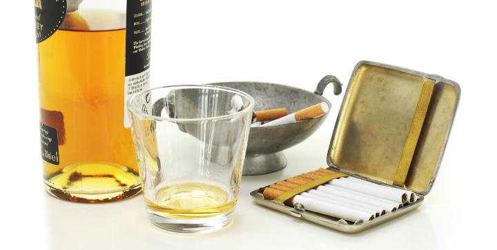 En flaske med alkohol, et glas og cigaretter.
