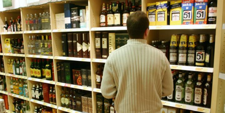 En mand der kigger på alkohol i en butik.