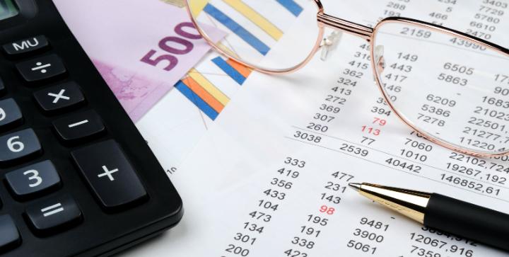 Lommeregner, penge, kuglepen, briller og papir.